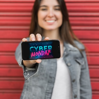 Mujer mostrando teléfono inteligente con foto de cyber monday