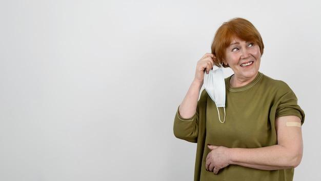 Mujer mostrando vendaje en el brazo después de la inyección de la vacuna