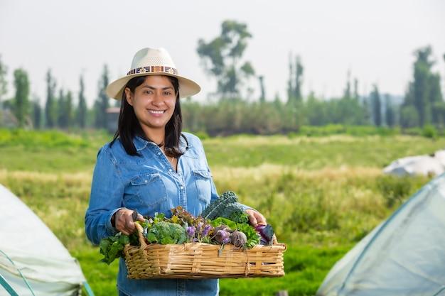 Mujer mostrando verduras en una canasta