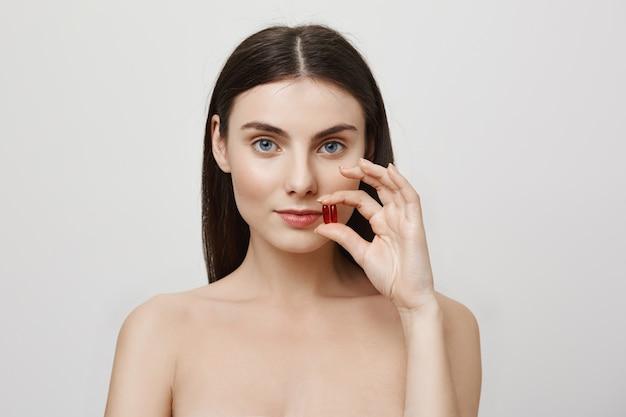 Mujer mostrando vitaminas, cuidando la salud