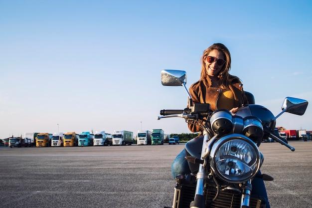 Mujer motociclista en chaqueta de cuero sentado en moto retro y sonriendo