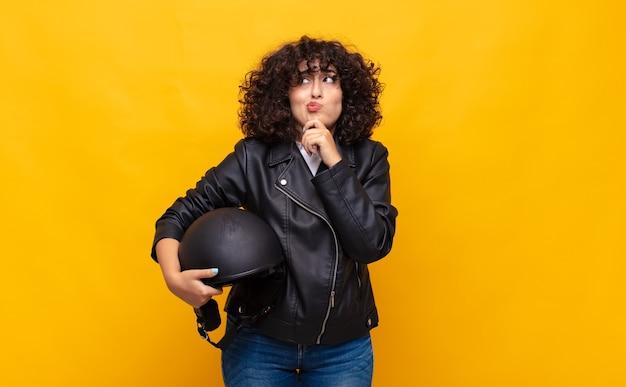 Mujer motociclista pensando, sintiéndose dudosa y confundida, con diferentes opciones, preguntándose qué decisión tomar