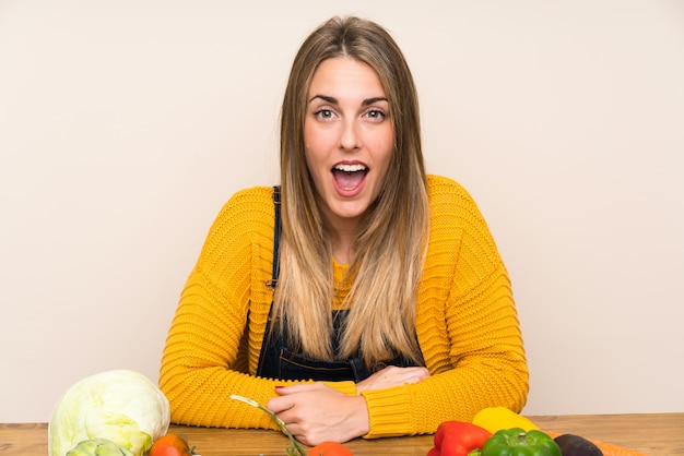 Mujer con muchas verduras con expresión facial sorpresa