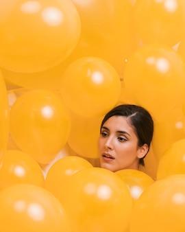 Mujer entre muchos globos amarillos