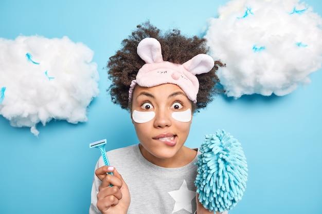 La mujer muerde los labios se siente avergonzada sostiene la navaja para depilarse la esponja de baño se somete a procedimientos de higiene se aplica parches de colágeno