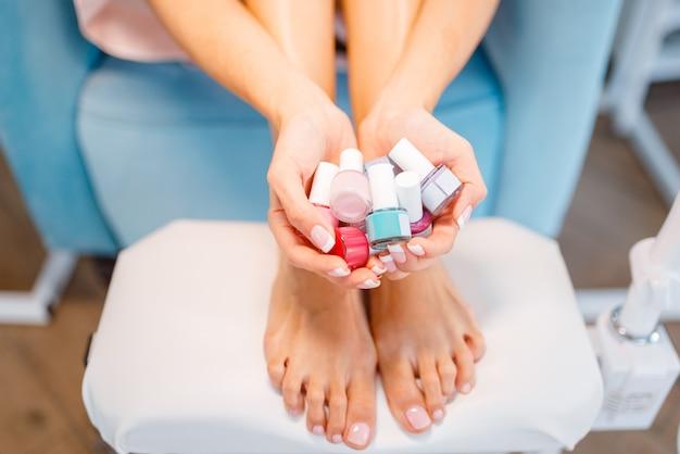 Mujer muestra muchas botellas de esmalte de uñas en salón de belleza. servicio profesional de manicura y pedicura, tratamiento de manos y piernas, cliente en salón de esteticista, persona femenina en la cosmetóloga