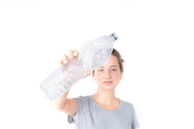 La mujer muestra y que sostiene la botella plástica reciclable aislada en el fondo blanco.