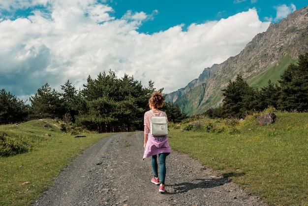 Mujer mujer feliz viajero caminando en campo con cielo azul en el paisaje