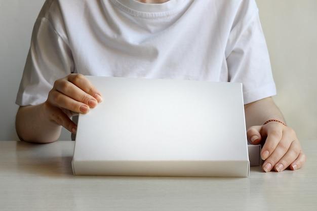 Una mujer, mujer, niña dos manos sostienen y abren el cuadro blanco vacío aislado blanco