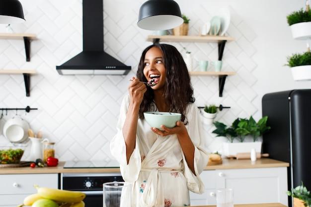 La mujer mulata atractiva sonríe está comiendo frutas cortadas en la moderna cocina blanca vestida con ropa de dormir con el pelo suelto desordenado