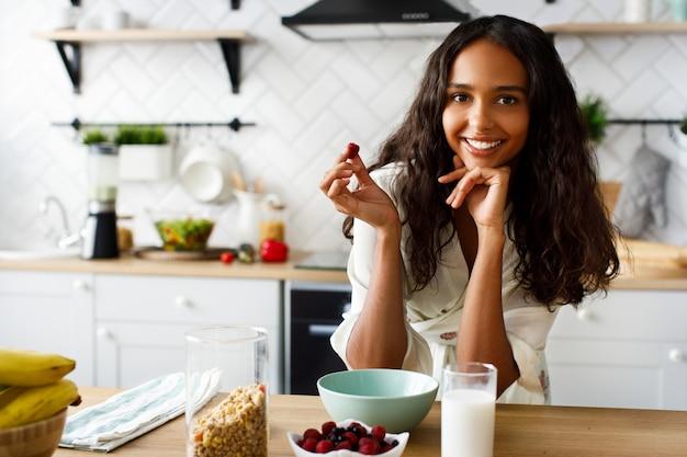 La mujer mulata atractiva sonríe sostiene frambuesa cerca de la mesa con un vaso de leche y crujientes en la moderna cocina blanca vestida con ropa de dormir con el pelo suelto y mirando directamente