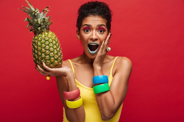 Mujer mulata en colorido atuendo emocionado mientras sostiene en las manos piña fresca y jugosa disfrutando de frutas aisladas, sobre pared roja
