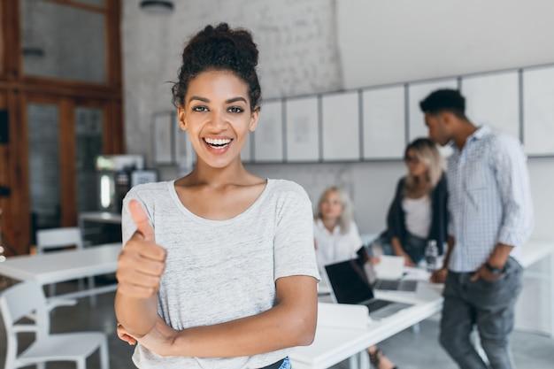 Mujer mulata emocionada con peinado rizado posando con el pulgar hacia arriba en la oficina. estudiante africana elegante divirtiéndose después de exámenes con amigos de la universidad detrás.