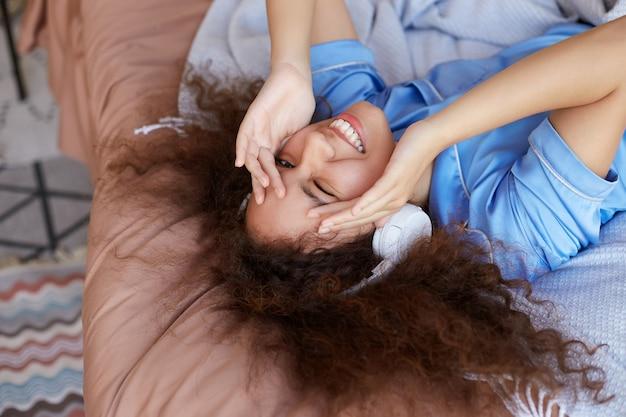 Mujer mulata rizada acostada en la cama con la cabeza gacha, escuchando su canción favorita en auriculares, sonriendo ampliamente, entrecerrando los ojos y tapándose el rostro del sol de la mañana.
