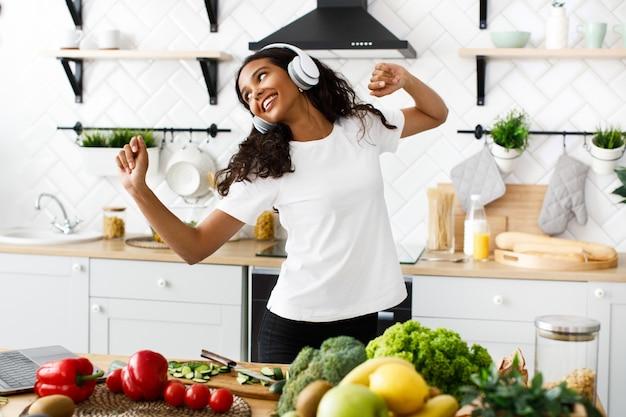 Una mujer mulata sonreída con grandes auriculares inalámbricos baila cerca de una mesa llena de frutas y verduras