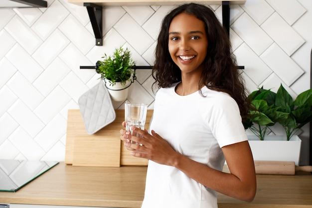 La mujer mulata sonríe sostiene un vaso con agua cerca del escritorio de la cocina en la moderna cocina blanca vestida con una camiseta blanca