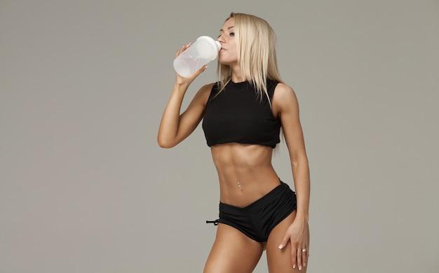 Mujer muscular deportiva agua potable, aislado sobre fondo gris
