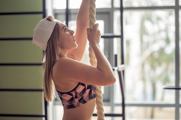 Mujer muscular haciendo cuerda de escalada en gimnasio en forma