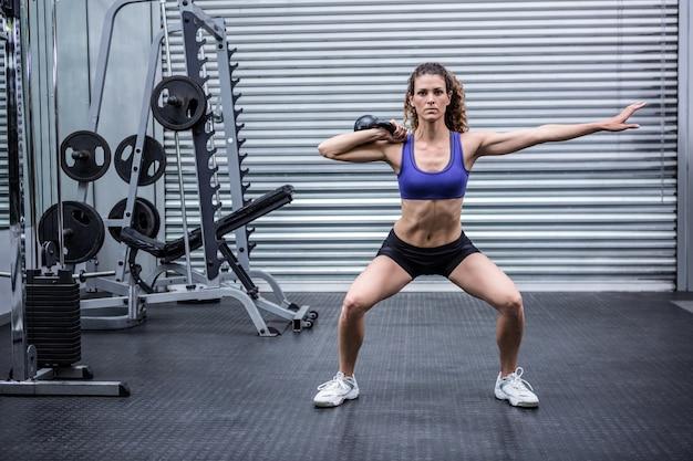 Mujer muscular que ejercita con kettlebells