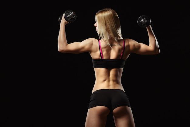 Mujer musculosa de espaldas levantando pesas sobre un fondo negro