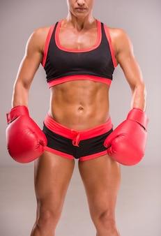 Mujer musculosa en guantes de boxeo