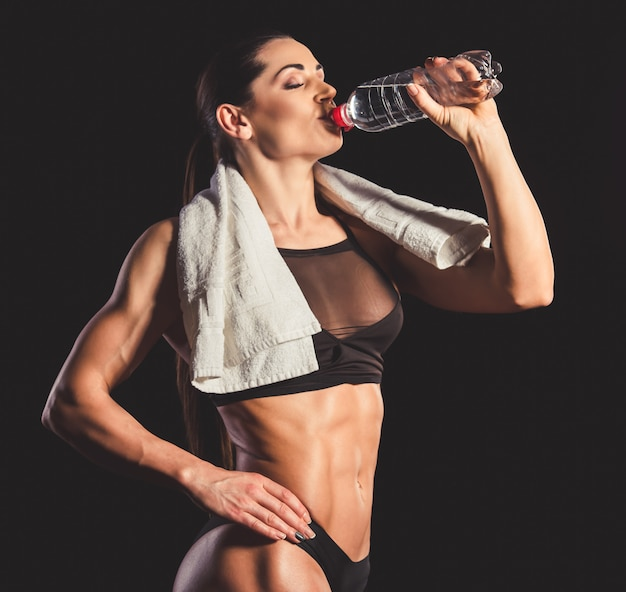 Mujer musculosa en ropa interior negra agua potable