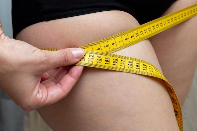 Mujer muslo de medición con cinta métrica amarilla. chequeo corporal. dieta fitness.