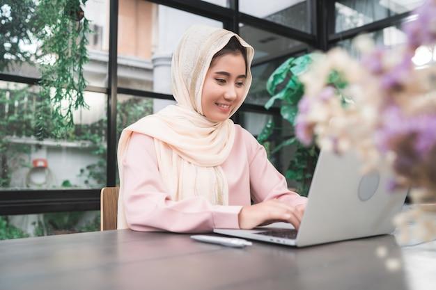Mujer musulmán asiática sonriente de los jóvenes hermosos que trabaja en el ordenador portátil que se sienta en sala de estar en casa