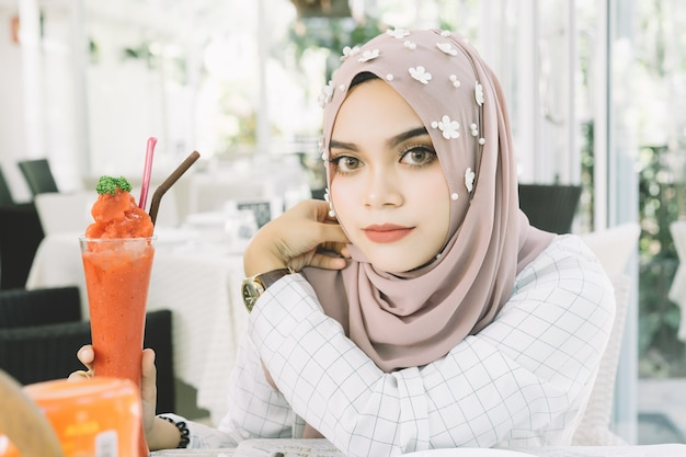 Mujer musulmán hermosa joven con el smoothie de la fresa en restaurante.