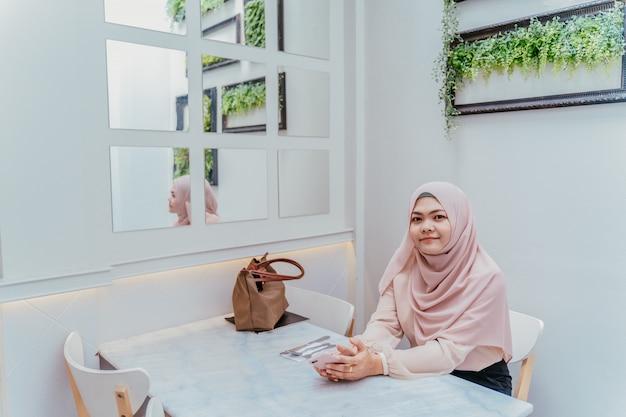 Mujer musulmán joven confiada que se sienta en la silla blanca y que se relaja en la cafetería el día de vacaciones.