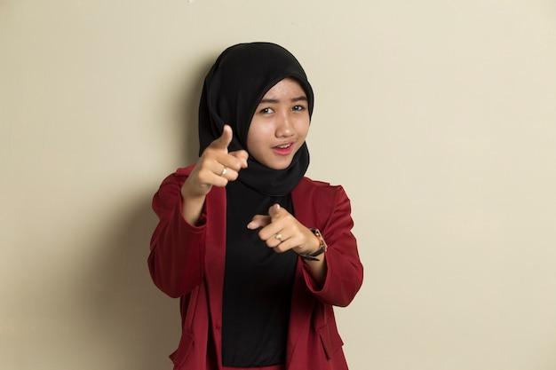 Mujer musulmana asiática en hijab sonriendo mientras apunta hacia adelante
