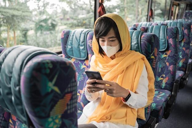 Mujer musulmana asiática con mascarilla usando su teléfono móvil mientras viaja en autobús