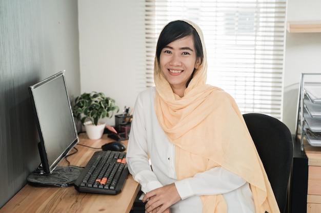 Mujer musulmana asiática que trabaja en su oficina