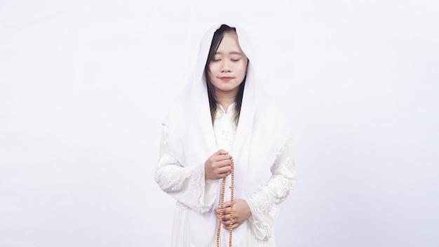 Mujer musulmana asiática con rosarios rezar con tasbih en blanco