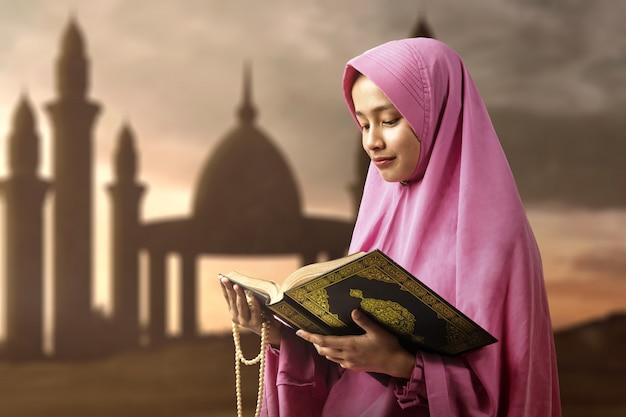 Mujer musulmana asiática en un velo con cuentas de oración y leyendo el corán