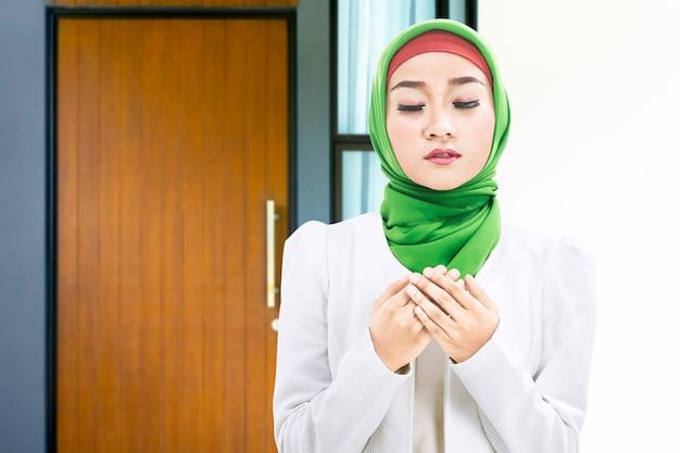 Mujer musulmana asiática en un velo de pie mientras levanta las manos y reza en casa