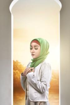 Mujer musulmana asiática en un velo de pie mientras levanta las manos y reza en la mezquita