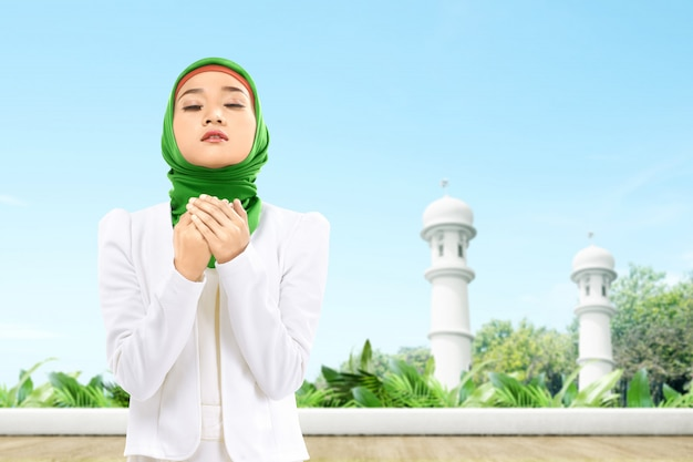 Mujer musulmana asiática en un velo de pie mientras levanta las manos y rezando