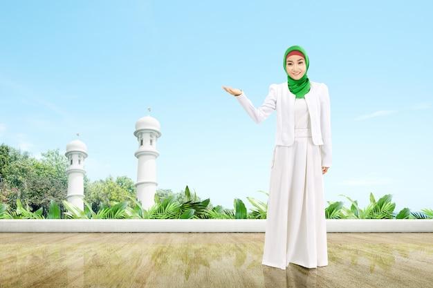 Mujer musulmana asiática en un velo de pie y mostrando la palma abierta