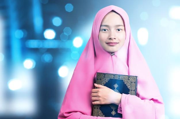 Mujer musulmana asiática en un velo de pie y sosteniendo el corán con fondo claro borroso