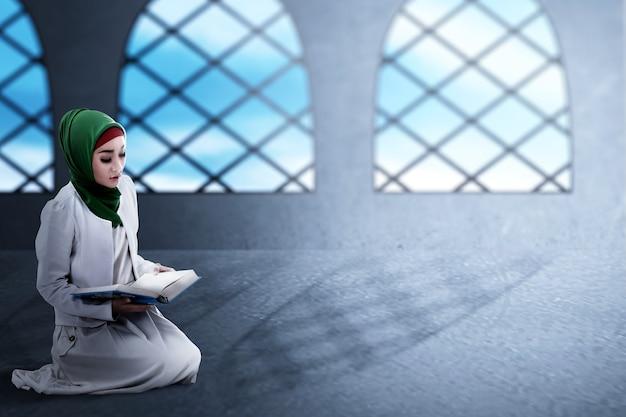 Mujer musulmana asiática en un velo sentado y leyendo el corán en la mezquita