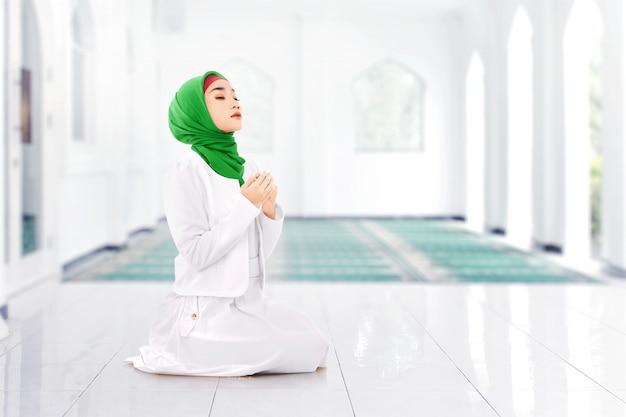 Mujer musulmana asiática en velo sentado en posición de oración mientras levanta las manos y rezando