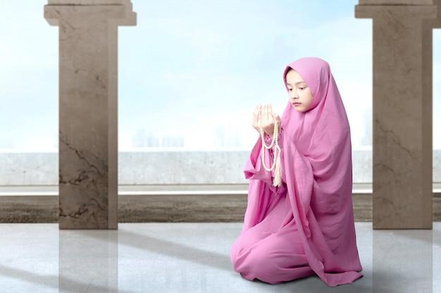 Mujer musulmana asiática en velo sentado y rezando con cuentas de oración en sus manos