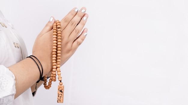 Mujer musulmana asiática vistiendo rosarios dando la bienvenida a los huéspedes o ied fitr saludo en un espacio en blanco