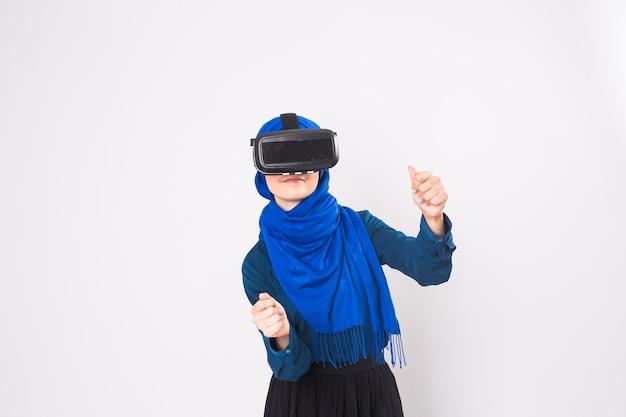 Mujer musulmana con auriculares vr. tecnología, vr, personas y concepto de juego.