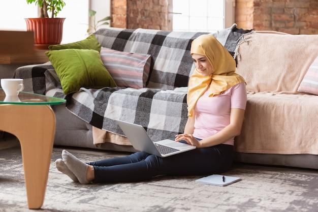 Mujer musulmana bastante joven en casa durante la cuarentena y el autoaislamiento, usando tableta para selfie o videollamada, lecciones en línea