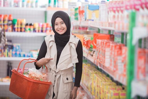 Mujer musulmana comprando algún producto halal