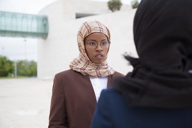 Mujer musulmana concentrada hablando con colega