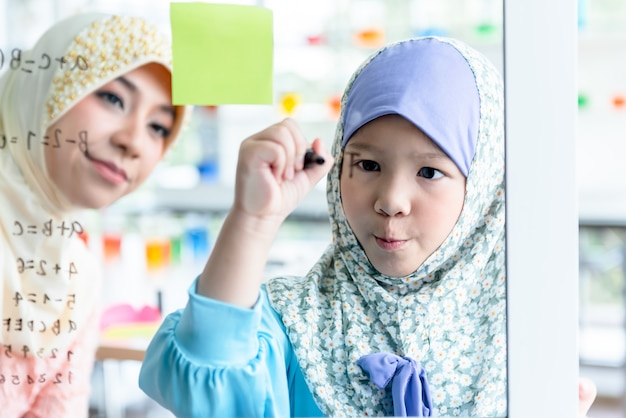 Mujer musulmana enseñando a los alumnos del niño escribiendo fórmulas matemáticas en una placa de vidrio en