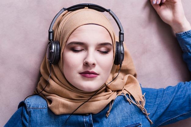Mujer musulmana escuchando música en auriculares
